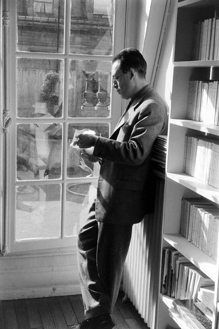 Albert Camus kitaplığın önünde.